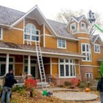 Rainbow Holiday Design installing Christmas Lights on two story home using a lift and ladders.