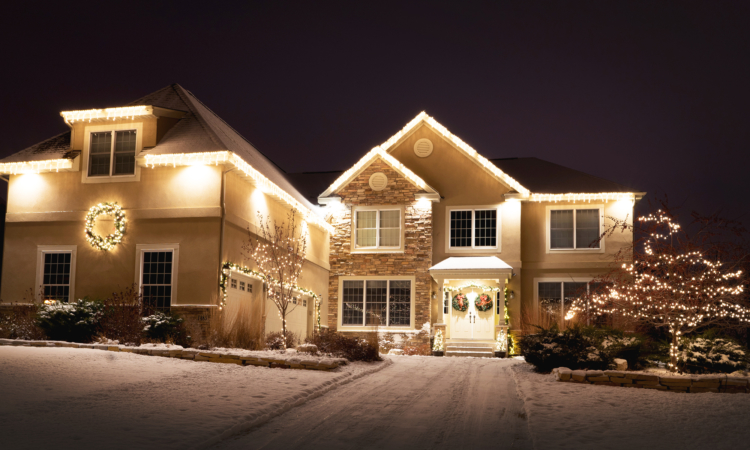 Two story house in Eagan, Minnesota with white lights along roof line, in two small trees, a wreath and garland.